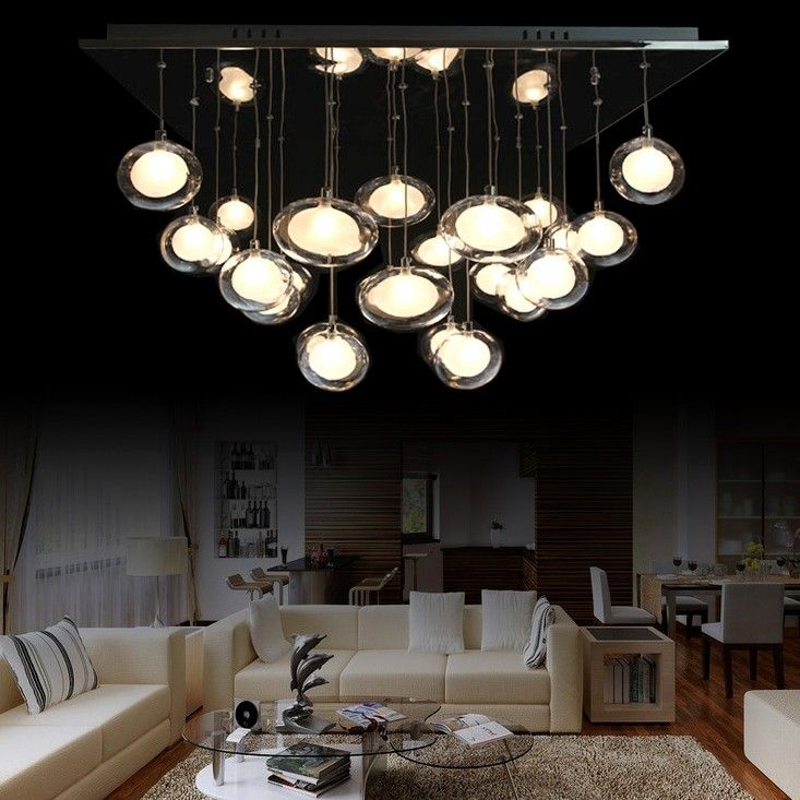 This contemporary ceiling fixture glows with beautiful materials and a spectacular design from Hena series. It features a chrome finish square ceiling canopy upon which a cluster twenty-five glass ovals are attached via cables. Brilliant halogen bulbs are nestled in pods of opal etched glass within larger pods of clear glass giving a sense of warmth and a welcoming look.
