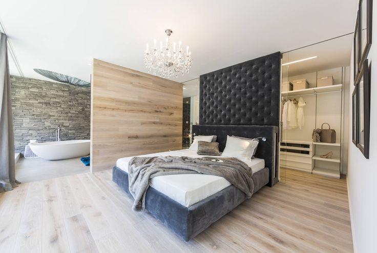 Studio bedroom with bathroom, large black padded headboard, and wooden floors