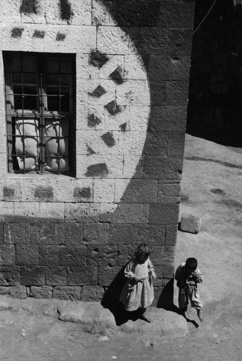 Ara Güler;  Van Gölü'nün kuzeybatı kıyısında sahil kenarında kurulu, Bitlis iline bağlı olan Ahlat ilçesi. Kötü ruhları uzak tutmak için özel bir tasarım ile boyanmış bir evin önünde oynayan çocuklar. 1956