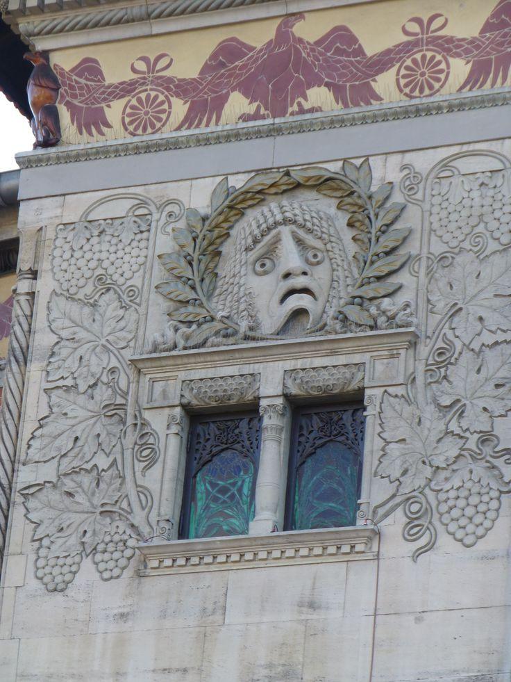 Den tragiske maske omkranset af laurbær. Vinrankerne rundt om refererer til Dionysos.