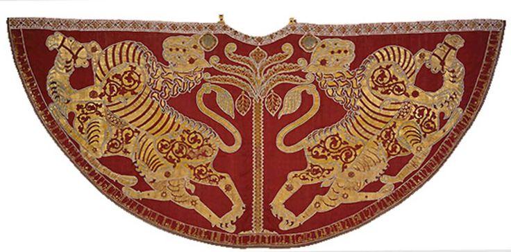 Mantello dell'Incoronazione di Ruggero II  Celebre questo, anche per il pubblico in generale, è noto forse più per il colore e il simbolismo che nemmeno per la sua storia in generale. Realizzato da un opificio islamico palernitano del XII secolo, il mantello fu realizzato in occasione dell'Incoronazione a Re di Sicilia di Ruggero II d'Altavilla. Il mantello, realizzato su seta rossa, ha ricami realizzati interamente in oro che vogliono rappresentare un leone che abbatte un cammello, un…
