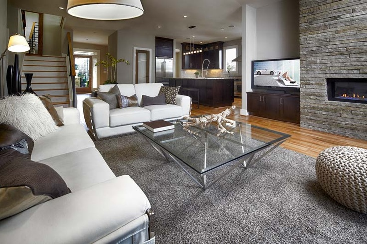 The family room of this new Modern Prairie style home in Candler Park features hardwood floors, custom modern fireplace with stone wall and built in TV cabinet.  The room opens to the kitchen which is perfect for entertaining!  Built by Epic Development; Interior Design by Amira Mamdani