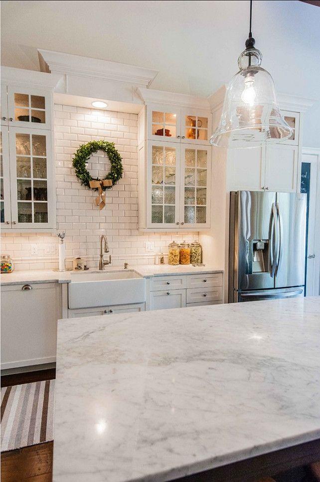 ガラスシェードのペンダントライトとガラス扉のウォールキャビネットのある白いキッチン