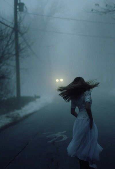 She could see a car approaching. Through the fog all she could see was the headlights, but that's all she needed. She took the opportunity and raced out from the trees, running towards the car. This could be her only chance at escape and she wasn't going to miss it.