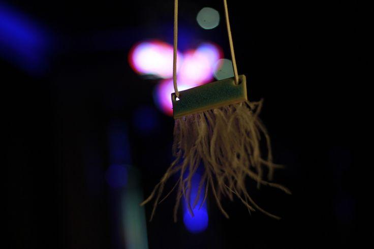 Beyaz seramik çamuruyla hazırlanmış, türkuaz sırlı kolye. Kuş tüyleri sentetiktir, yapımı için hayvanlara zarar verilmemiştir. www.azimeozgen.com