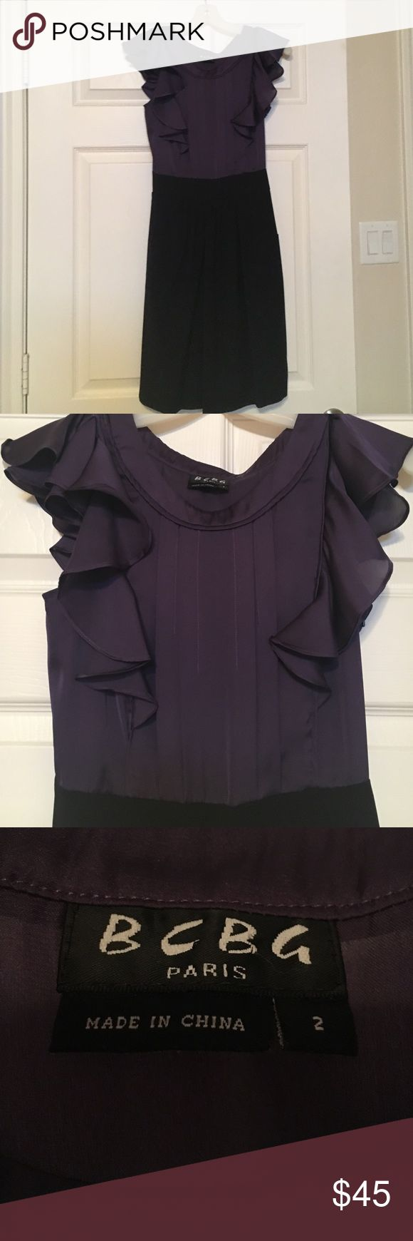 BCBG Purple and Black Dress Purple and black BCBG dress. The top is satin with ruffled sleeves. The bottoms is slightly pleated in front and has pockets! BCBG Dresses Mini