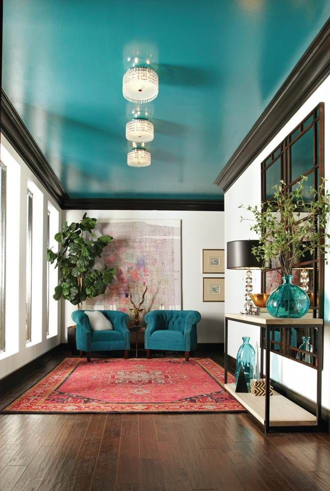 White walls are accented with striking black molding and a glossy turquoise ceiling