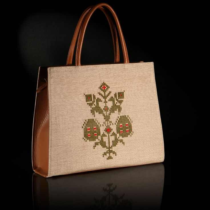 """Anthemis"" is a handmade woven bag decorated by a pattern inspired of a traditional outfit of Astipalaia. The color of the leather is tan, background's color is ecru-beige and the traditional pattern is in olive green shade."