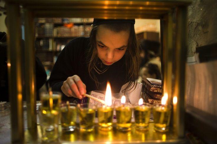 Un niño judío ultra-ortodoxo de la familia Krois enciende velas para la fiesta judía de Hanukkah en es casa en el barrio de Mea Shearim de Jerusalén 22 de diciembre de 2014. (Foto por Ronen Zvulun / Reuters)