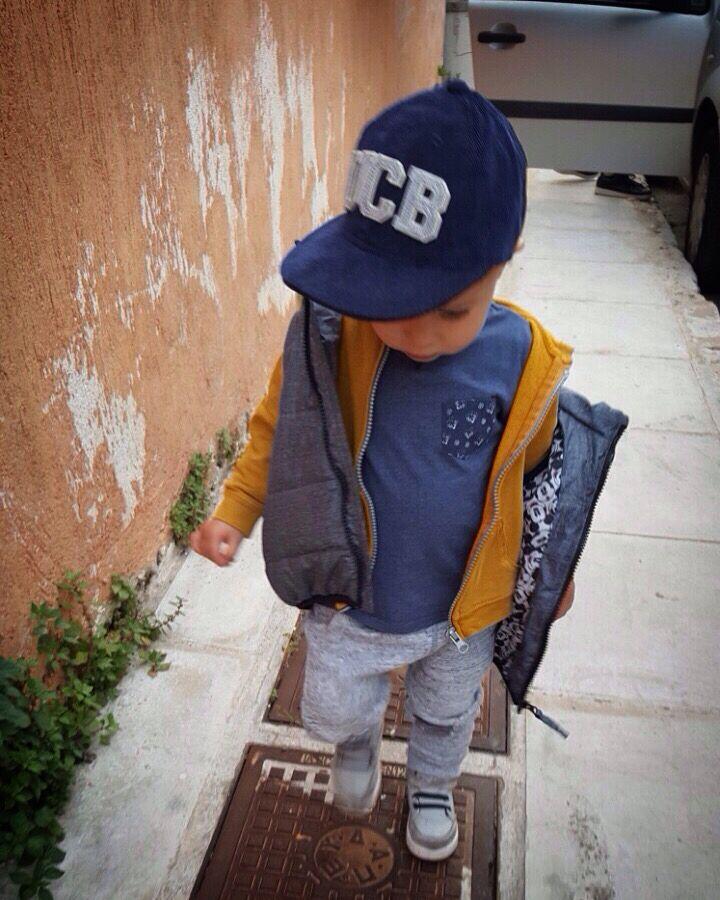 Little boy wearing blue hat and sneakers .