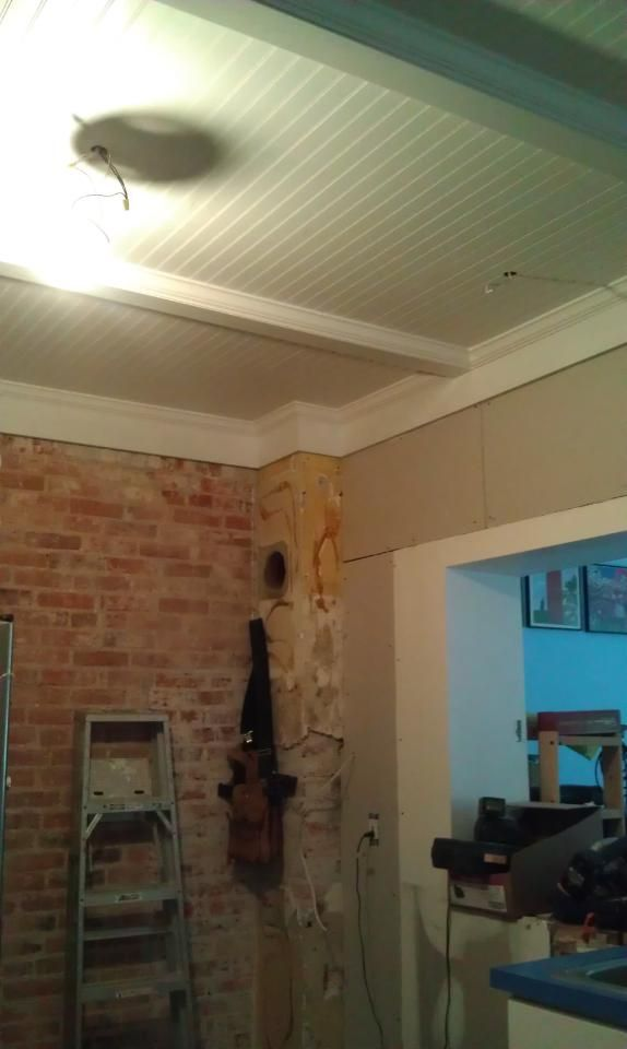 they removed a drop ceiling and replaced with beadboard between beams