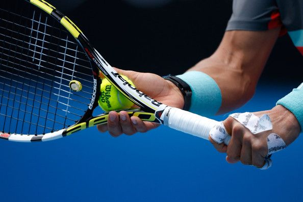 Details of hands on Rafael Nadal of Spain as he serves in his fourth round match against Kei Nishikori of Japan during day eight of the 2014...