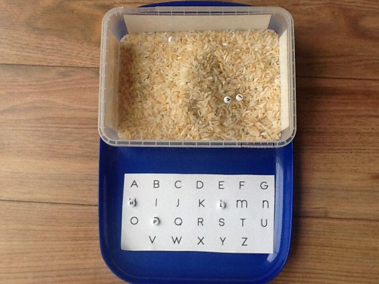 Verstop kraaltjes met letters in een bakje met rijst. Nu zoeken maar: het alfabet, je naam, de eerste letter van de plaatjes voor je neus..