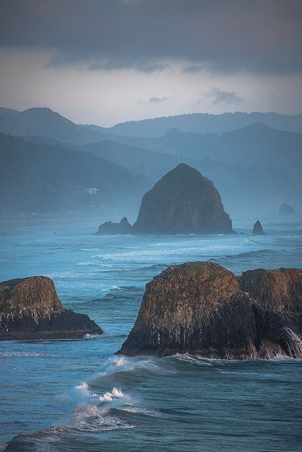 """Haystack Rock is a 235' sea stack located at Cannon Beach, Oregon.  Composed of basalt it was formed by lava flows from the Grand Ronde Mountains 10-17 million years ago; it was once joined to the coastline but years of erosion have since separated the monolith from the coast (three smaller, adjacent rock formations to the south are collectively called """"The Needles"""") by Bobshots on Flickr."""