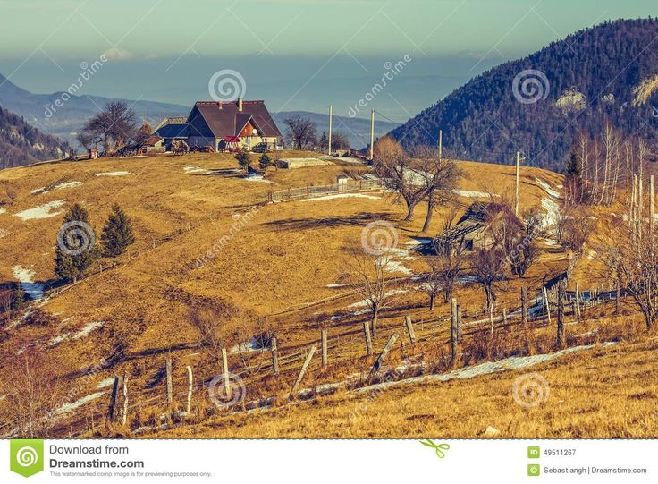 Peaceful Romanian rural scene with traditional farm and grassland uphill in Moeciu, Brasov county, Trasylvania region, Romania.