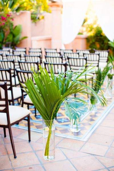 Palm tree leaves in tall vases line this aisle: http://www.stylemepretty.com/2014/12/03/retro-island-inspired-hawaii-wedding/ | Photography: Acqua Photo - http://acquaphoto.com/