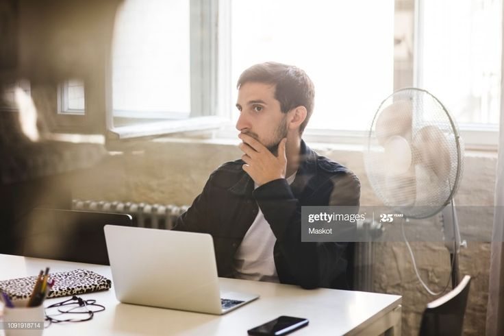 Businessman Listening While Sitting In Conference Room ...