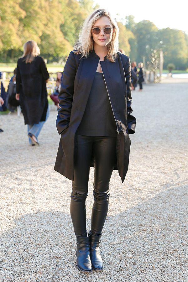 Elizabeth Olsen usa calça resinada e look todo preto, com sobretudo e ankle boot.