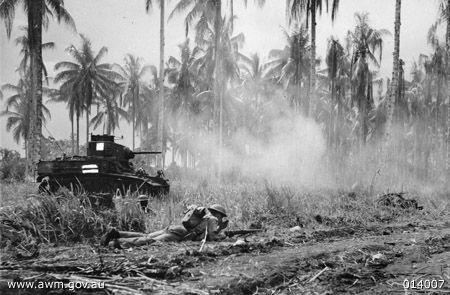 Australian Company Sergeant Major McCominski and Private M. Daniels waited as the accompanying M3 General Stuart tank attacking a Japanese pillbox, near Buna, New Guinea, 2 Jan 1943