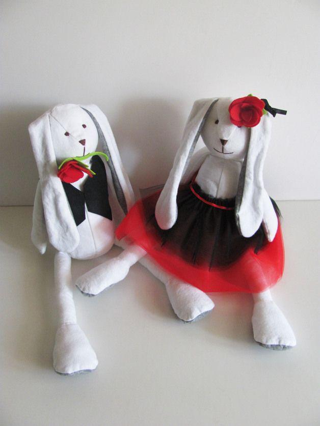 I nostri Coniglietti si sono dati al Tango!  Questa adorabile coppia di coniglietti è una perfetta idea regalo per una coppia di entusiasti del ballo, o una decorazione originale per una casa accogliente.  Il ballerino indossa un gilet nero e porta una rosa rossa tra i denti, chiaramente per sedurre la partner. Lei indossa una gonna a due strati di tulle decorata con un nastrino rosso di raso, e una rosa in testa abbinata.