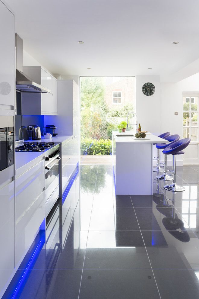 """""""This simple squared kitchen design is brought to life by the neon blue strip LED lighting beneath the cabinets and the island. APD Interiors have also used a reflective tiled floor which only helps to exaggerates the lighting."""""""