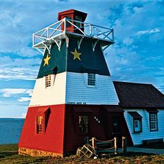 Coastal Living Magazine | This New Brunswick lighthouse sports the colours of the Acadian flag. Now used as a tourism center, it stands on the edge of the Bay of Chaleur on Route 11 in Grand-Anse.