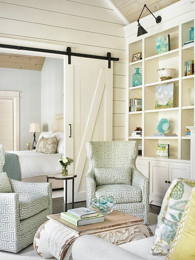.A great conversation area with a barn door on tracks, coastal colors, and an accent wall highlighting collectibles. JD
