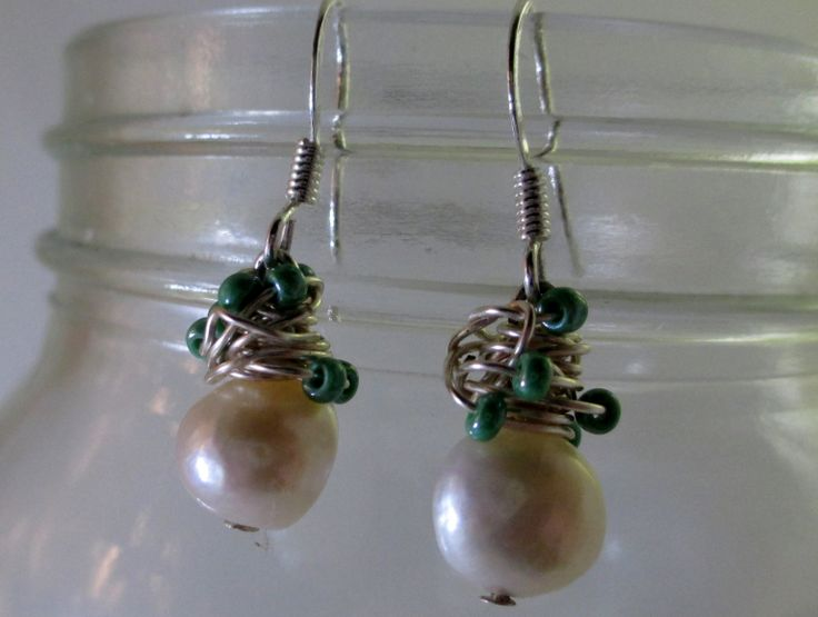 Handmade by me.White 9-10mm freshwater pearl wrapped with silver-plated wire and sea foam green seed beads.  Silver plated fish hook finding.  Simple and classy!