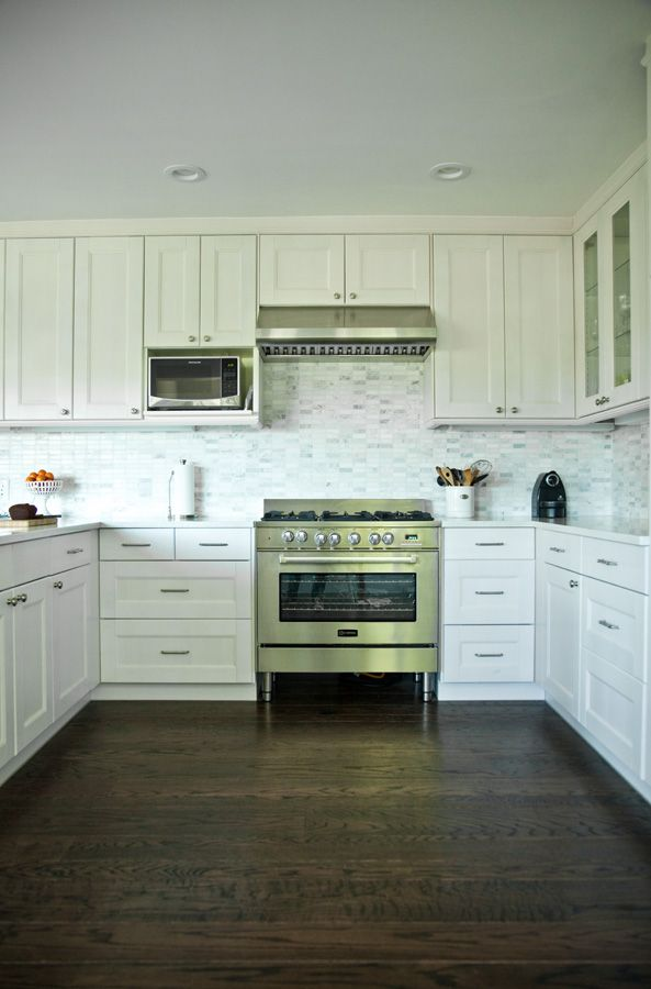 ikea cabinets look classy alongside a marble mosaic backsplash and high end appliances