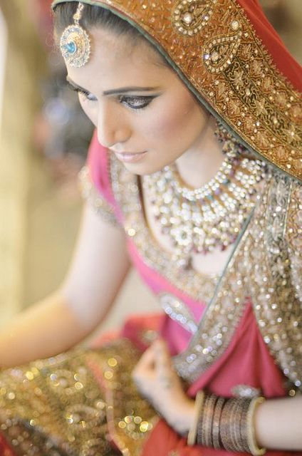 A Pakistani Bride, in traditional dress and jewlery.  Bride normally wear different shades of red on her Barat; the wedding day.