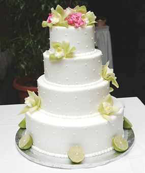 Brides: White Wedding Cake With Flowers. For dessert, the couple offered their guests a four-tier lemon wedding cake with raspberry filling and a selection of petite pastries.