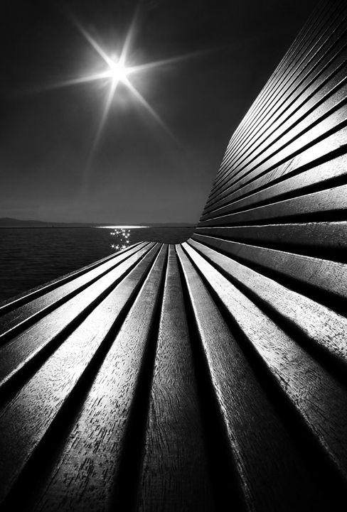 "Banca en una playa, convertida en maravillosa escultura de fugantes. ""Sunny Bench"" por Marzena Wieczorek."