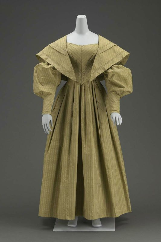 """Going away dress and matching cape, 1838 US, the Museum of Fine Arts, Boston    Newly wedded couples change into """"going away"""" outfits before leaving their reception.  This tradition is fading in most places, but it's still hanging on here in the South.        Dress (a) and matching cape (b) of grayish-olive-green silk with fancy-woven stripes with lines of white; fitted bodice, pointed in front; widely flaring neck; fullness across bust in unpressed pleats; long sleeves with fine pleats in…"""