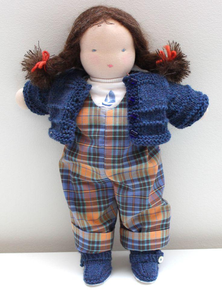 Bambola steineriana da i capelli marroni, con salopette, scarpe con suola in feltro, mutande, maglietta con stencil - con golfino blu (in vendita a parte) In vendita sul sito www.rudolfsteiner.it/shop