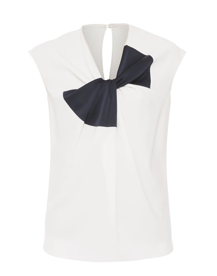 Add a hint of feminine allure to your new season wardrobe with this Paule Ka top. Crafted from a luxurious sateen-backed crepe fabric, this blouse is designed with a black appliqué bow that contrasts with its crisp white color. Pair yours with a pair of white trousers and pointed heels for an effortlessly elegant look.
