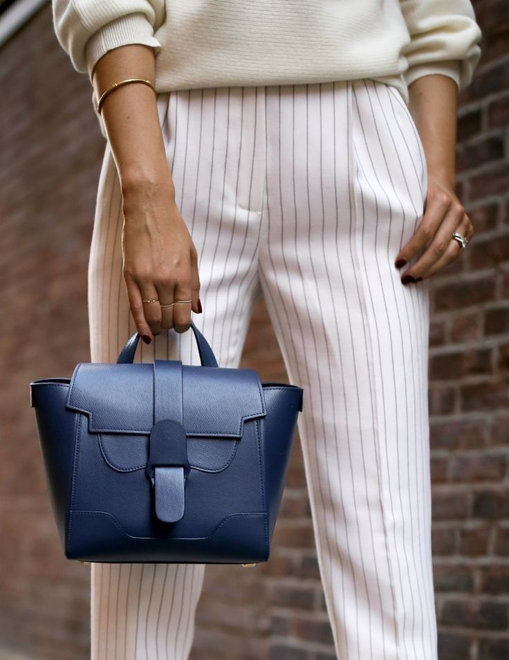 THIS HANDBAG LINE IS COMPLETELY CHANGING THE WORK BAG GAME // Cream off the shoulder sweater, white pinstripe tapered pant, bow sandals, navy mini Maestro work bag {Theory, Senreve, Alexandre Birman, professional style, day to night, work bag, work tote, classy dressing, wear to work style, office style}