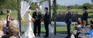 Lovely outdoor ceremony at local golf course, complete with flower garnished arbor | www.EvermooreFilms.com