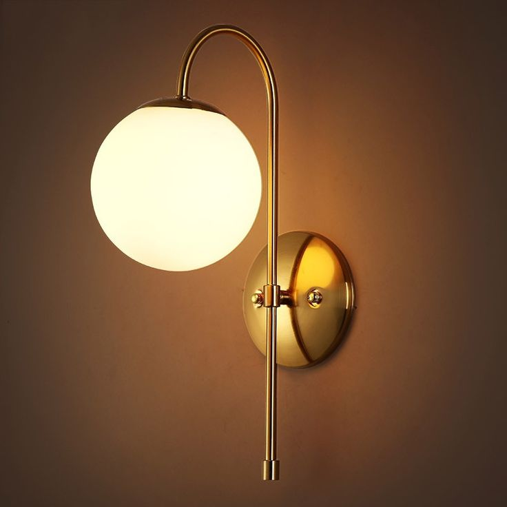 Minimalist metal curved arm aged brass single light indoor sconce with round backplate indoor wall lights wall lights lighting