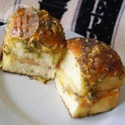 Snelle en makkelijke warme broodjes voor een hele groep. De bolletjes worden belegd met ham en kaas en bestreken met een mengsel van boter, suiker, gedroogde ui en maanzaad en dan gebakken in de oven, tot de kaas is gesmolten. Delen maar!