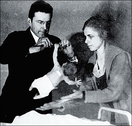 Dr John B. Watson and Rosalie Raynor studying the grasp reflex of a newborn baby. Baltimore. ca 1916-1920.