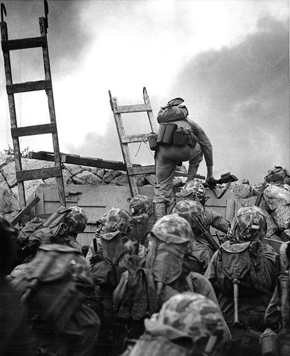 First Lieutenant Baldomero Lopez USMC leads the 3rd Platoon Company A 1st Battalion 5th Marines over the seawall on the northern side of Red Beach as the second assault wave lands 15 September 1950 during the Inchon invasion. Wooden scaling ladders are in use to facilitate disembarkation from the LCVP that brought these men to the shore. Lt. Lopez was killed in action within a few minutes while assaulting a North Korean bunker. Note M-1 Carbine carried by Lt. Lopez M-1 Rifles of other…