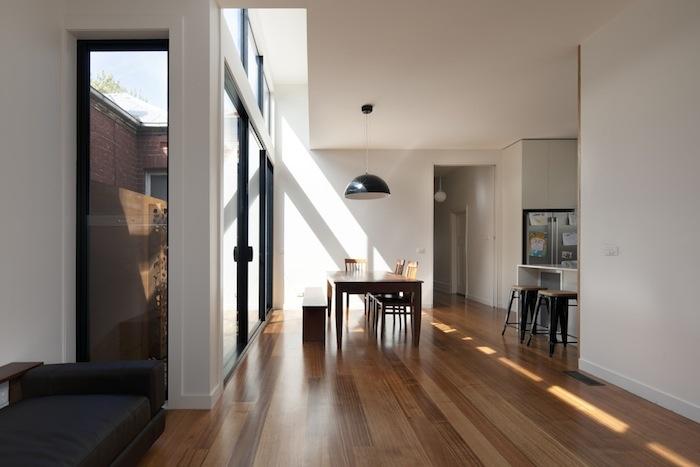 Black aluminium, white trim, floor boards and white walls