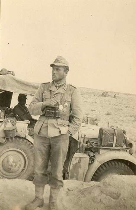 A soldier standing next to his staff car while serving with the Afrika Korps