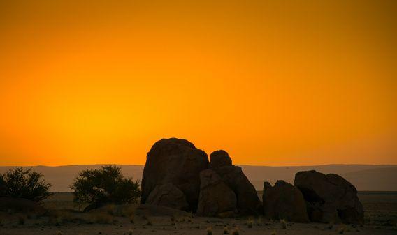 De zon gaat onder achter de rotsen in de Namib woestijn
