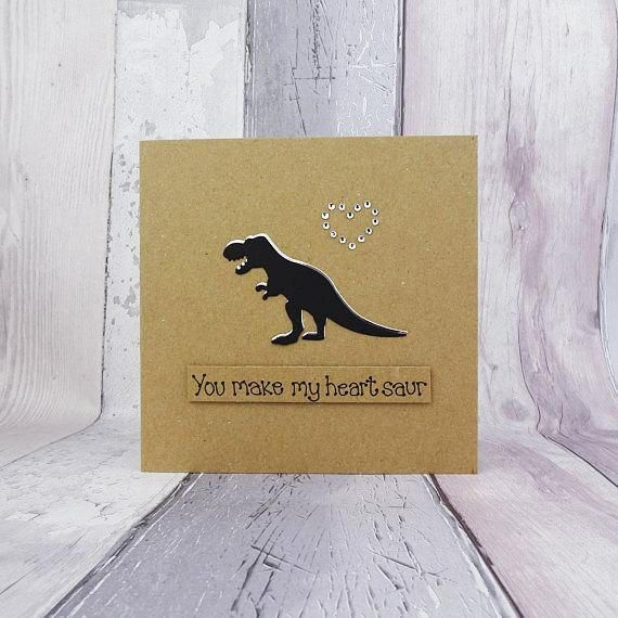 Handmade dinosaur love card. This sweet T-Rex card would make a great anniversary, Valentines Day or even birthday card for the special someone in your life. This romantic card with a pun has a silhouette of a Tyrannosaurus Rex with gems in the shape of a heart. The colour of the shadow of the T-Rex and the gems can be selected from the drop-down menu on this handmade dinosaur card. The sentiment on this card is added with 3D foam and reads: You make my heart saur! This message can be…
