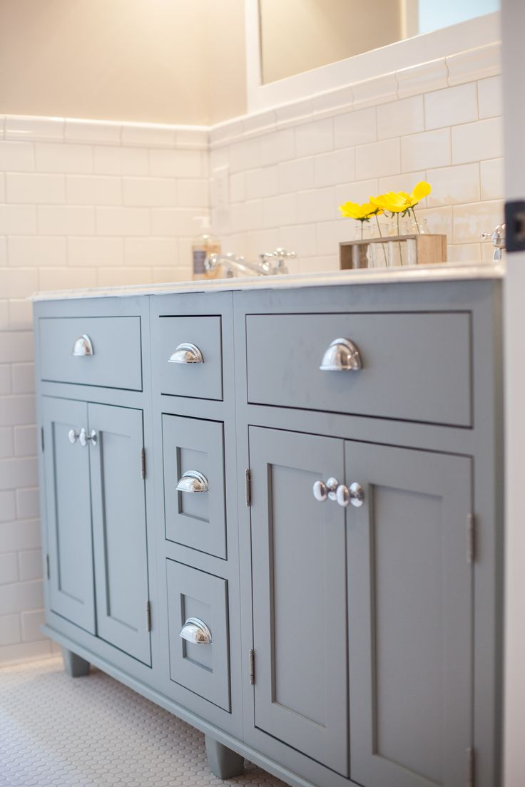 gorgeous bathroom boasts gray dual sink vanity accented with nickel knobs and cup pulls topped with white marble with ogee edge framing his and her sinks