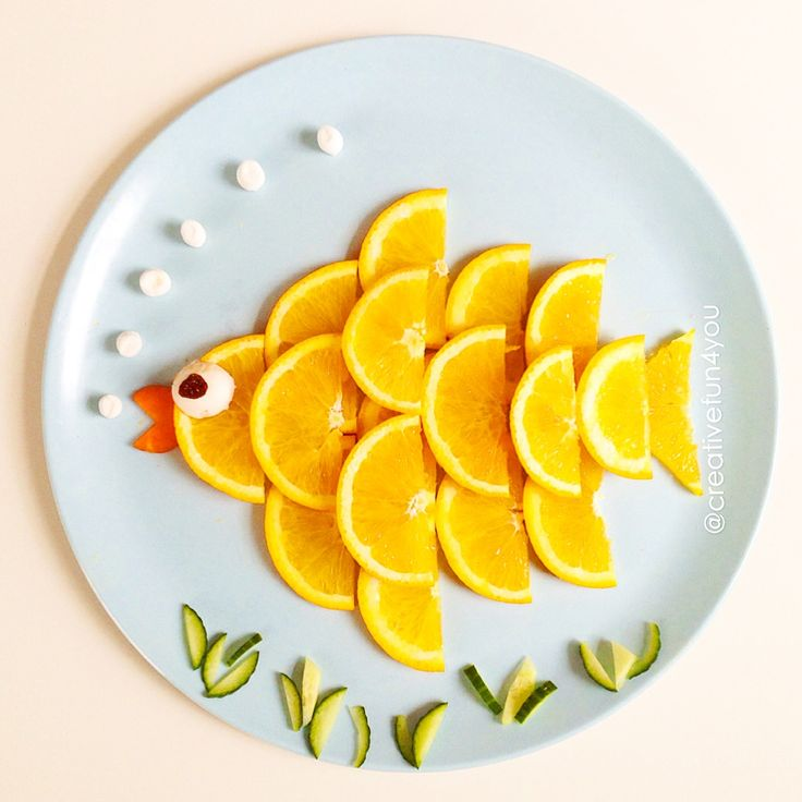 Translated from Norwegian: Orange fish. Cut up orange slices, and then in two. Place them over each other as shown in the picture. Mouth of the fish is made of carrot, while the eye is a mushroom and a raisin. The bubbles are made of mini-marshmallows!