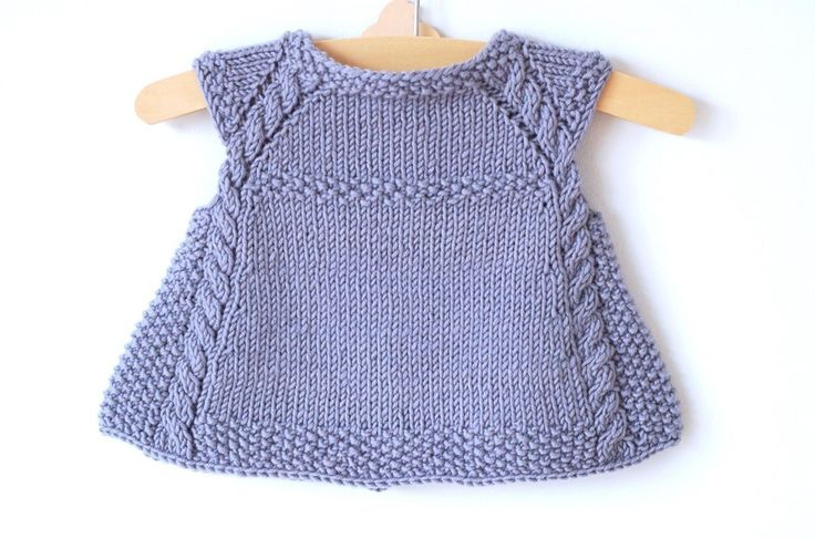 This charming cap-sleeved, swingycardigan is the perfect timeless piece to add to any little girl's summertime wardrobe, or as an extra layer in the Fall. Lovely over a crisp white dress, it iscomfortable enough to be paired with everyday play clothes.The cables and seed stitch create a sophisticated, rich texture that is designed toshowcaseyarns with greatstitch definition.This cardigan is knit seamlessly from the top down. Stitches for the cap sleeves are bound off, then the front...