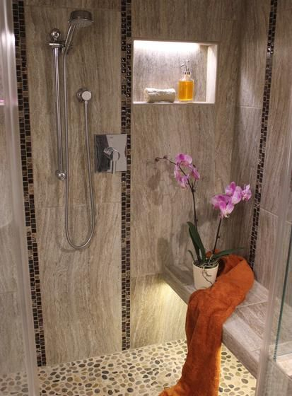 Rustic Stone Shower With Lines Of Dark Tile On The Walls