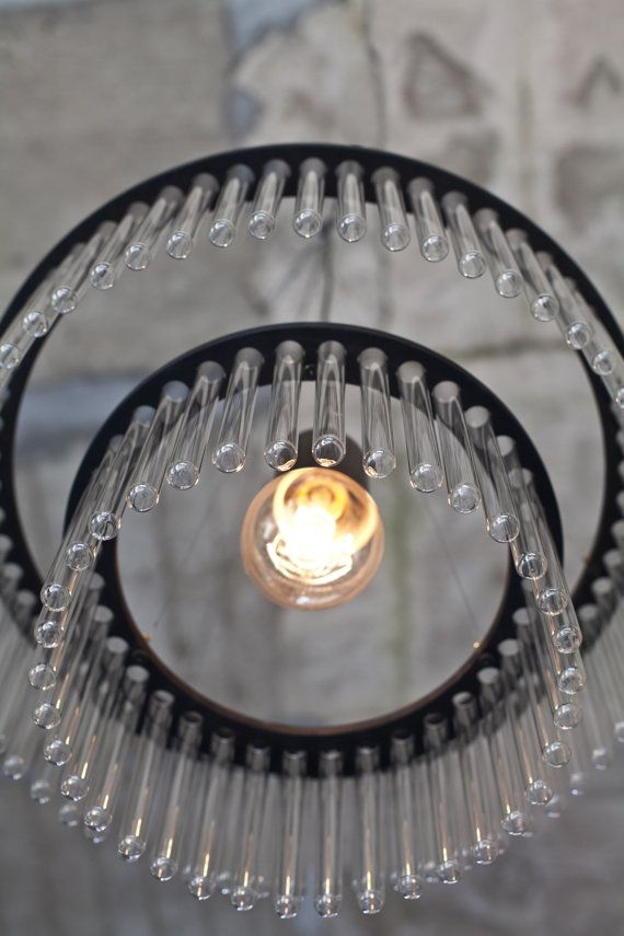Maria S.C. chandelier is glamorous black. Maria S.C. chandelier is made from laboratory test tubes, set in two plywood bands. This surprising material